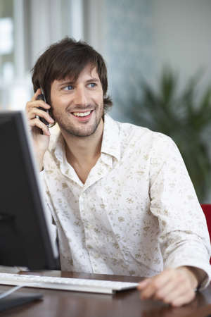 homeoffice: Man Using Computer and Cellular Phone
