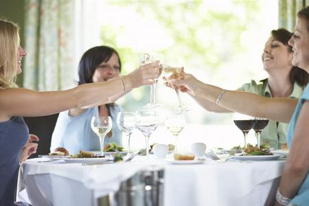 achievment: Women Toasting in Restaurant LANG_EVOIMAGES