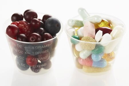 comparable: Berries and Pills in Medicine Cups
