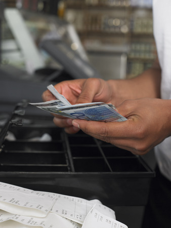 merchant: Man Couting Cash in Register LANG_EVOIMAGES