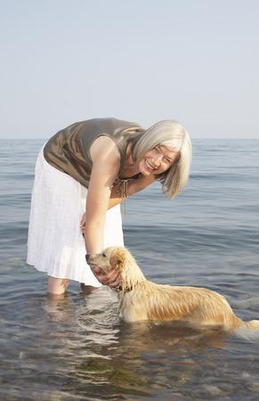 oceanic: Woman Petting Dog in Water