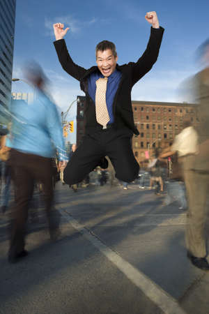 Businessman Jumping for Joy at Downtown Intersection LANG_EVOIMAGES