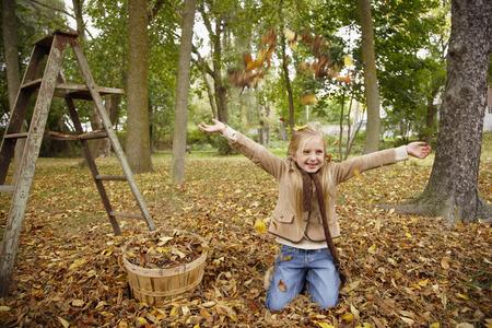 vómito: Niña que lanzan las hojas de otoño en el aire