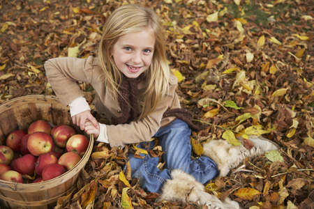 sitting on the ground: Portrait of Gril sitting in Autumn Leaves with Basket of Apples
