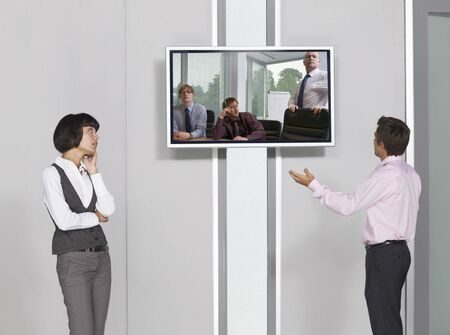 perturbed: Business People Videoconferencing with Big Screen Television LANG_EVOIMAGES