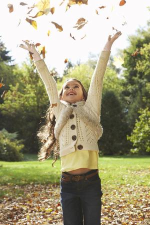 vómito: Chica arrojando hojas en el aire