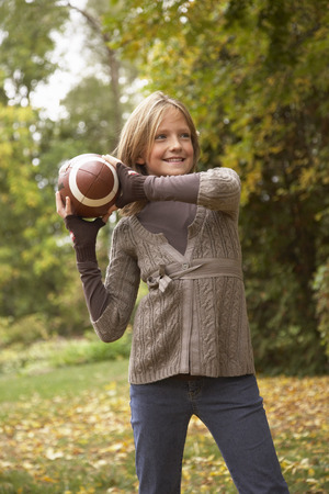 vómito: Retrato de niña lanzando fútbol americano, en otoño