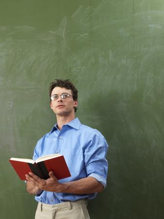 vocational high school: Teacher with Book in Front of Blackboard
