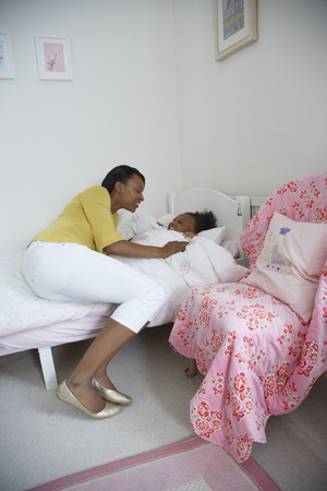Mother Tucking Daughter into Bed