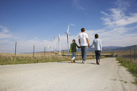 Father and Children Walking on Rural Road, next to Wind Turbines