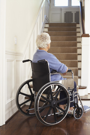 Senior Woman in Wheelchair at Bottom of Stairs LANG_EVOIMAGES
