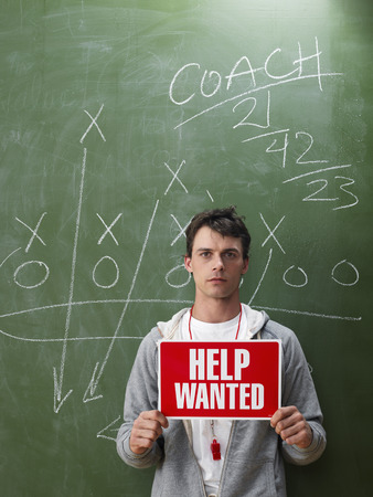vocational high school: Coach Holding Help Wanted Sign