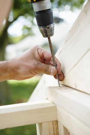 Close-up of Mens Hands using Cordless Drill