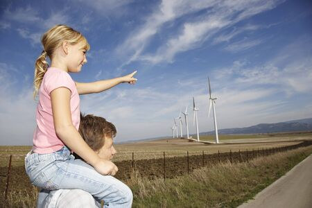 Young Girl on Fathers Shoulders Pointing at Wind Turbines LANG_EVOIMAGES