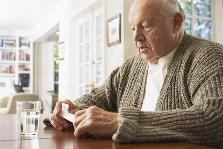 Senior Man Looking at Pill Organizer