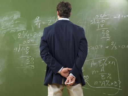 vocational high school: Teacher Looking at Math Problems on Blackboard