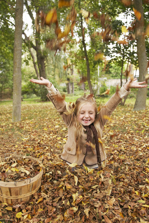 sitting on the ground: Girl Throwing Autumn Leaves in Air LANG_EVOIMAGES