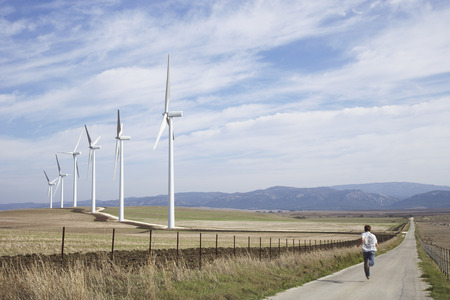 expressing: Boy Running on Rural Raod, next to Wind Turbines LANG_EVOIMAGES