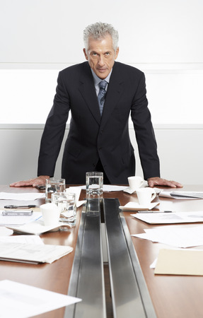 achievment: Businessman at Messy Boardroom Table