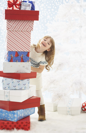 Girl Stacking Christmas Presents LANG_EVOIMAGES