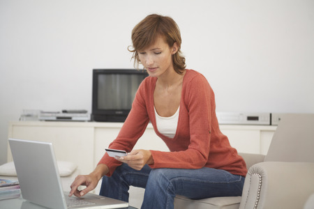 Woman in Living Room with Credit Card and Laptop Computer LANG_EVOIMAGES