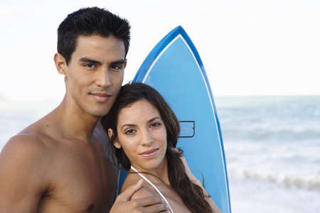 Portrait of Couple With Surfboard LANG_EVOIMAGES
