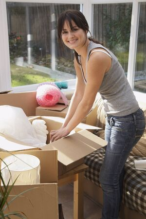 sunroom: Woman Packing Boxes in Sunroom LANG_EVOIMAGES