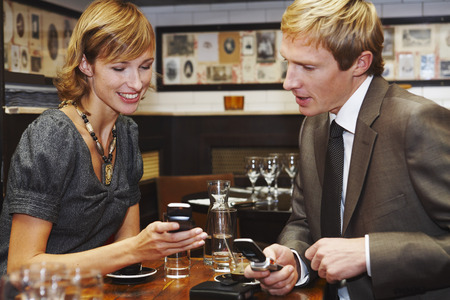 to pulsate: Couple with Cell Phones in Cafe