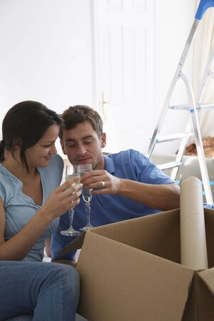 end of a long day: Couple in New Home with Boxes and Champagne