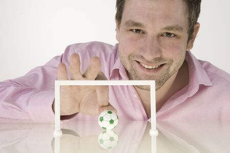 Businessman Playing With Miniature Football