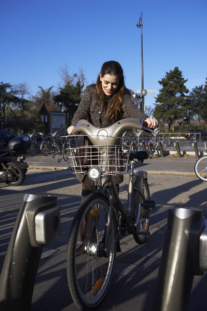environmental issues: Woman Renting Bicycle, Paris, France