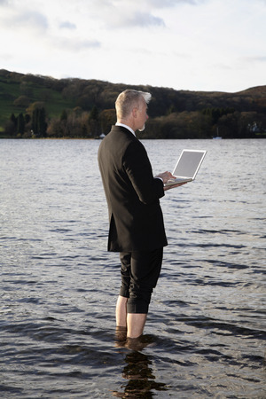 Businessman with Laptop Computer Standing in Lake Windermere, Cumbria, England LANG_EVOIMAGES