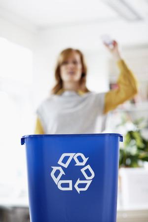 vómito: Mujer lanzando papel en la papelera de reciclaje
