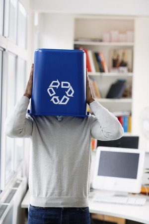 environmental issues: Businessman with Recycling Bin over Head