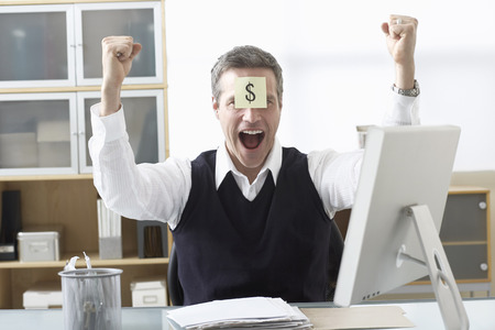 Businessman Sitting at Desk with Self Adhesive Note on Forehead