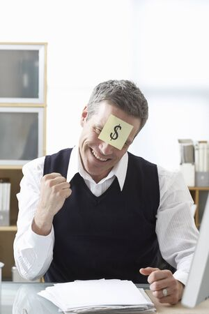 expressing: Businessman Sitting at Desk with Self Adhesive Note on Forehead