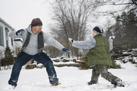vómito: Padre e hijo teniendo una pelea de bolas de nieve LANG_EVOIMAGES