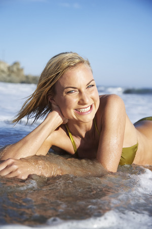 oceanic: Close-up Portrait of Woman Lying in the Water at Beach
