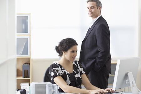 leer: Businessman Looking over Businesswomans Shoulder LANG_EVOIMAGES