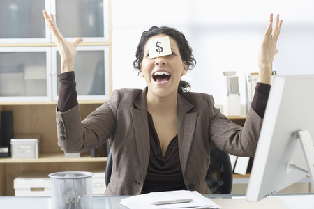 Businesswoman Sitting at Desk with Self Adhesive Note on Forehead LANG_EVOIMAGES