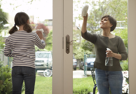Mother and Daughter Cleaning Windows of French Doors LANG_EVOIMAGES