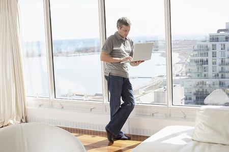 Man with Laptop in Condominium LANG_EVOIMAGES