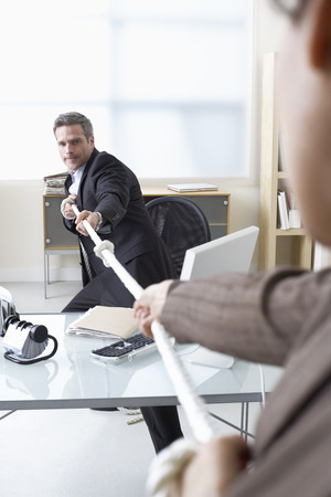 Business People in Tug-of-War at Desk
