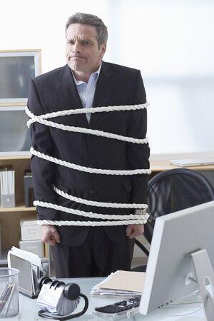 Businessman Tied Up with Rope at Desk LANG_EVOIMAGES