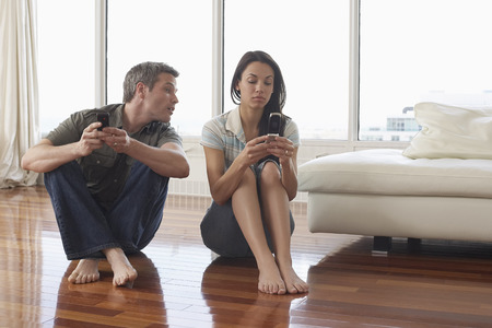 Couple with Cellular Phones in Condominium LANG_EVOIMAGES