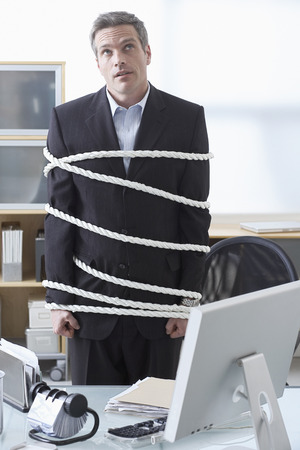 Businessman Tied Up with Rope at Desk LANG_EVOIMAGES