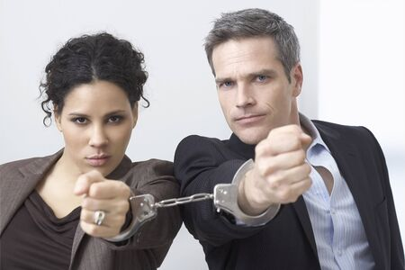 interdependence: Businessman and Businesswoman Handcuffed Together