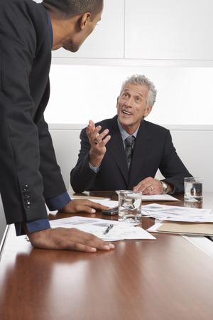 explained: Businessmen Talking in Boardroom LANG_EVOIMAGES