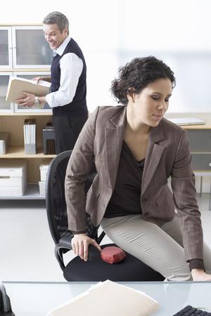 harassing: Businessman Playing Practical Joke on Businesswoman LANG_EVOIMAGES