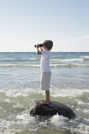 Boy on the Beach Looking Through Binoculars, Elmvale, Ontario, Canada
